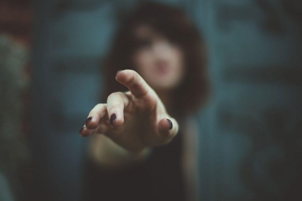 Donna sfocata con mano in primo piano